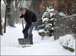 New York City Mayor Bill de Blasio shovels the side- walk in front of his house in New York. New York City public schools were closed after up to 7 inches of snow fell in the Big Apple's first snowstorm of winter.