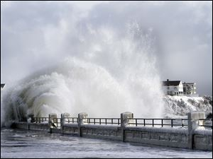 Heavy surf breaks over the seawall after a winter storm in Hampton, N.H. Some cities in the New England region reported having accumulations of more than 2 feet of snow as of Friday.