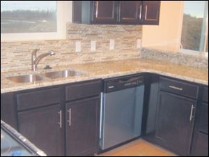 Granite countertops meet with tiled backsplash in neutral tones.