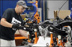 An employee works on suspensions for the new Jeep Cherokee at the Toledo Assembly Complex.