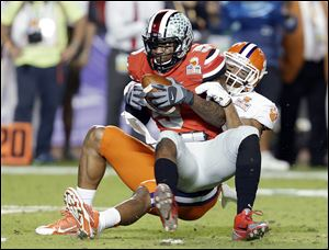 Ohio State quarterback Braxton Miller is brought down by Clemson defensive end Vic Beasley during the first half of the Orange Bowl.