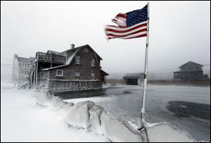A tattered flag flies by a flooded yard along the shore in Scituate, Mass. today. A blustering winter storm that dropped nearly 2 feet of snow just north of Boston.