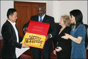 In this 2011 photo, Mayor Mike Bell, center, accepts a gift from Zhao Talimu of Beijing Conservatory. To the mayor's left is  Kathy Carroll, Toledo Symphony president, and Amy Chang, associate principal cellist.