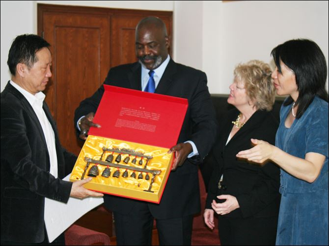n7bell In this 2011 photo, Mayor Mike Bell, center, accepts a gift from Zhao Talimu of Beijing Conservatory. To the mayor's left is  Kathy Carroll, Toledo Symphony president, and Amy Chang, associate principal cellist.