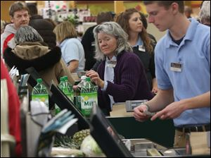 Cashier Anna Clark, center, checks out a customer who stocked up on pop at The Andersons' Maumee location.