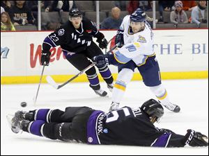 Toledo Walleye player David Gilbert (10) shoots over a sliding Reading Royals player Mike Banwell (5) during the third period.
