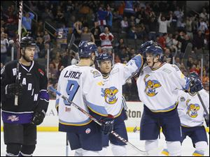 Toledo Walleye players Kevin Lynch (9), Ryan Flanigan (32) and Louis-Marc Aubry (25) celebrate Aubry's game-winning goal.