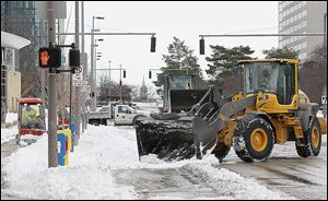 City crews work to remove snow in downtown Toledo near the corner of Superior and Jackson streets in preparation for the next snowstorm, which will be the third one of the season so far.