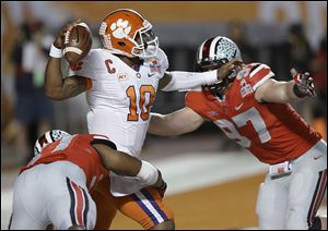 Clemson quarterback Tajh Boyd looks to pass as he is pressured by Ohio State's Joshua Perry, left, and Joey Bosa, a freshman, who hurt his ankle in the game, but had five tackles and one sack.