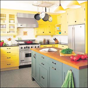 Paint your kitchen workhorse an accent color. This dark green balances walls lined with warm-yellow cabinets and creates a strong visual impact.
