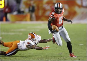 Ohio State quarterback Braxton Miller runs past Clemson's Robert Smith for a touchdown in the Orange Bowl. He threw for 2,094 yards and ran for 1,068 this season.