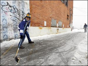 Ben Wielgopolski, 13, left, and Jeremy Fry use a parking lot to get in some hockey practice on Adams Street near 11th.