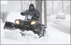 Lewis Gonzales uses his four-wheeler to plow snow from the sidewalks on North Erie Street near Galena Street near Jamie Farr Park in North Toledo. Sunday afternoon's temperatures remained comfortable for such outside work and play in the region.