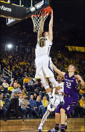 Michigan guard Nik Stauskas dunks the ball above Northwestern forward Nathan Taphorn. Stauskas led the Wolverines with 18 points in Sunday's victory.