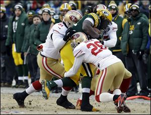Green Bay Packers running back Eddie Lacy gets tackled by San Francisco 49ers defensive end Ray McDonald, left, and cornerback Tramaine Brock.
