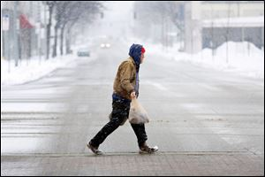 A lone man carries groceries across N. Michigan Street during a snowstorm on Sunday.