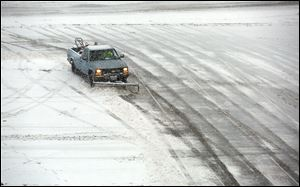 Plows work on emptying the parking lot at Franklin Park Mall after it closed early during a snow storm Sunday.