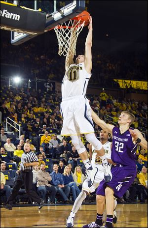 Michigan guard Nik Stauskas (11) dunks the ball while trailed by Northwestern forward Nathan Taphorn (32) in the first half Sunday in Ann Arobr.