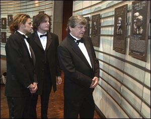 In this Oct. 4, 2001 file photo, Phil Everly, right, of the musical duo The Everly Brothers, looks at his plaque in the Country Music Hall of Fame along with his sons, Chris, left, and Jason, in Nashville, Tenn.