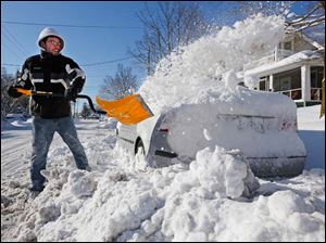 Adam Tober shovels snow from around his car on Broadway in Toledo.
