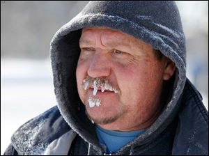 Icicles hang from the mustache of Brian Aiken after he used his snow blower to clear snow on front of his home on Broadway.