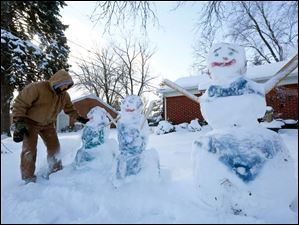 Steve Stachowiak, clears off the four bathing-suit clad snow people he and his family created Sunday in Toledo.   Stachowiak said he used spray paint to make the bikini and one piece bathing suit sculptures.