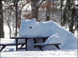 A large snow bear is seen on a picnic bench in Walbridge Park in Toledo.