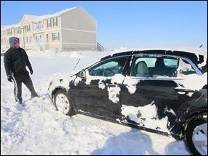 Ethan Binger, of Bowling Green, gets ready to push a car out of the snow at the Copper Beach Townhomes.