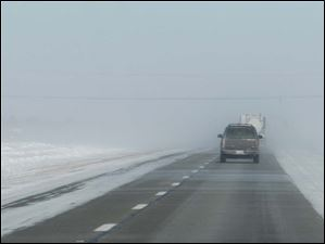 The fog of snow reduces visibility along northbound I-75, north of Bowling Green.