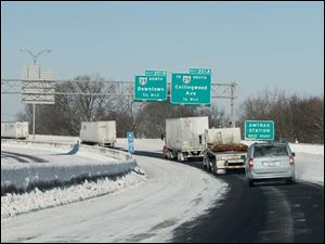 Vehicles in the southbound, left, and northbound lanes of I-75 just south of downtown Toledo stay in one lane each as drifting snow and freezing temperatures make snow-covered lanes icy.