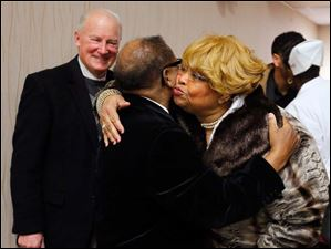 The Rev. Isiah James Johnson gets a hug and a kiss from Ella Joiner as members of St. Mark Baptist Church meet for service. At left is former mayor Carty Finkbeiner.