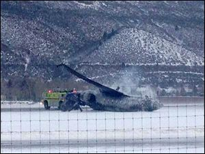 Emergency crews respond as a small plane lies on a runway at Aspen Airport in western Colorado after it crashed upon landing Sunday.
