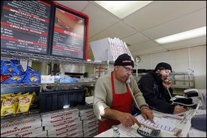 Bambino's Pizza co-owner Hassan Awada, left, and manager Tynan Rubin field two phone lines Monday to take pizza orders from customers who didn't want to venture out into the cold for food.