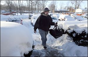 Bambino's Pizza employee Mike Broadbent battles the cold to deliver a pizza to a customer Monday. Deliveries were restricted to the immediate Toledo area.