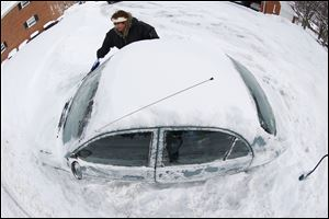 In an imagge made with a fisheye lens, Marguerite Johnston uncovers her car in Grosse Pointe, Mich. Michigan residents are preparing for diving temperatures as they dig out from more than 15 inches of snow in places.