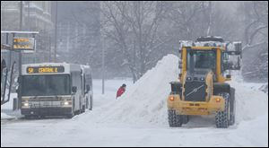 TARTA picks-up passengers on Jackson Street at the same time plows clear the street during a Level 3 snow emergency.