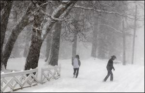 A couple walks through the winter white-out on Swan Avenue in Webster Groves, Mo., Sunday.