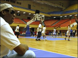 Dennis Rodman watches court side as North Korean and U.S. basketball players practice in Pyongyang, North Korea today.