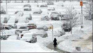 A woman walks back to her car in the long term parking lot at Indianapolis International Airport, Monday.