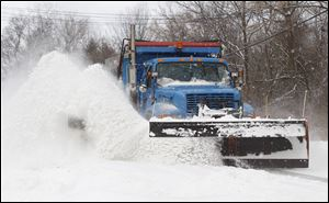 A plow throws snow