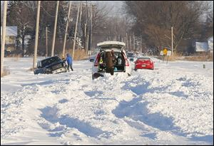 Three vehicles try to dig their way out of the snow on Suder Avenue. near Lotus Drive in Erie, Mich. today.
