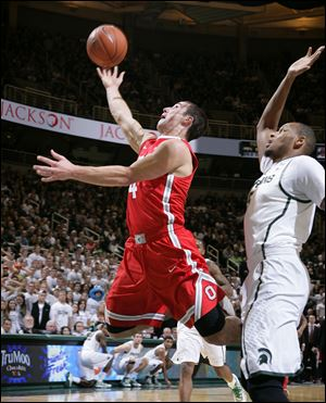 Ohio State's Aaron Craft, left, puts up a layup against Michigan State's Adreian Payne during the first half . Craft was instrumental in getting the Buckeyes to overtime, but his effort wasn't enough.