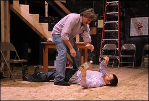 Glen Ackerman (who plays the roles of Selsdon Mowbray and Burgler) stands over Doug Kruse (filling the roles of Garry Lejeune and Roger) as they rehearse a scene from the Toledo Repertoire Theatre's production of 'Noises Off.'