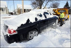 Jim Piasecki of Piasecki Service Inc. prepares to tow a car off Olson Street into the owner's drive so city crews could plow the Toledo street.