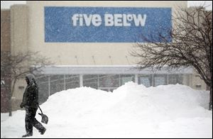 A man walks through while shoveling the parking lot in front of the Five Below shop in Fairview Heights, Ill.