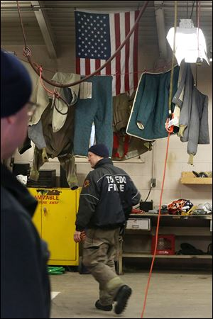 Toledo firefighter Bill Bruss passes by drying firefighting clothing hung inside the truck bay at the Station 9 firehouse in South Toledo.