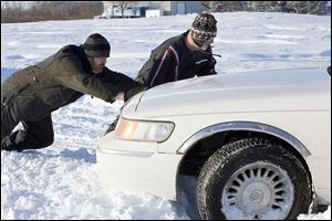 Mike Butzin, left, and Mark Oden of Point Place stop to help Marie Hayter, not pictured, of Temperance, Mich., get out of a snowbank where she was stuck on Suder Avenue near Lotus Drive in Erie, Mich.
