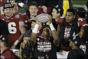 Florida State's Jameis Winston celebrates with The Coaches' Trophy.