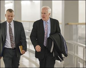 Senate Minority Whip John Cornyn, R-Texas, walks to the Senate through an underground tunnel on the way to a scheduled procedural vote in the Senate on a bill that would extend unemployment benefits, at the Capitol in Washington, Monday.