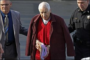 Former Penn State University assistant football coach Jerry Sandusky, center, leaves the Centre County Courthouse after attending a post-sentence motion hearing in Bellefonte, Pa. in January, 2013.